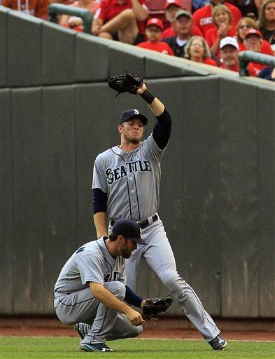Seattle Mariners' Michael Saunders, top, catches a fly ball hit by Cincinnati Reds' Zack Cozart as he tries to avoid running into teammate Nick Franklin in the first inning of their baseball game in Cincinnati, Friday July 5, 2013. (AP Photo/Tom Uhlman)