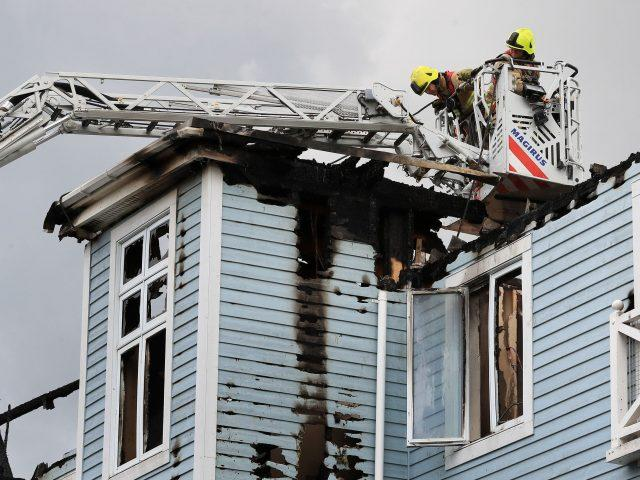 Firefighters examine the building