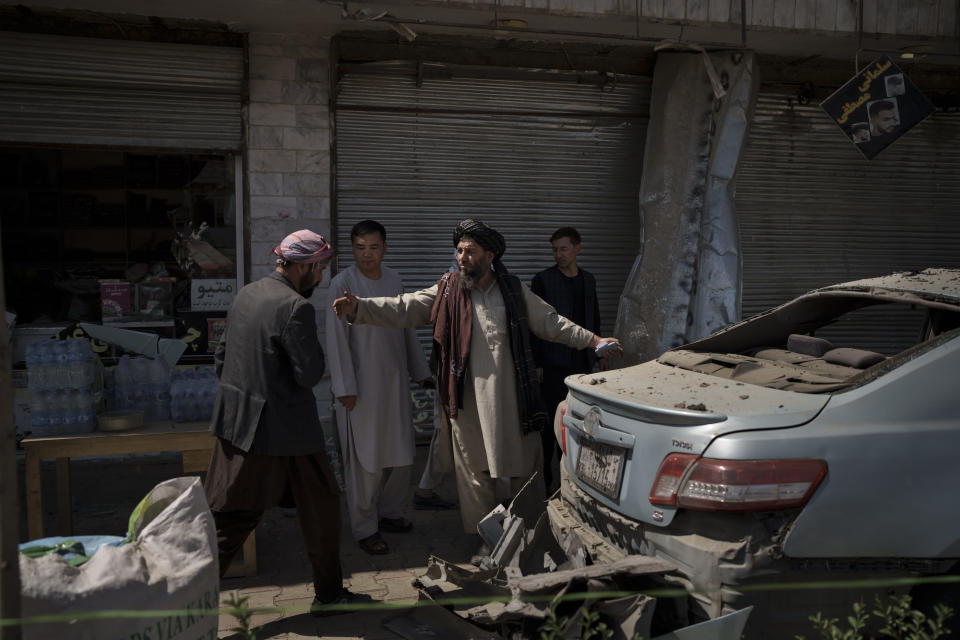 Taliban fighters and residents gather at the site of an explosion in Kabul, Afghanistan, Saturday, Sept. 18, 2021. A sticky bomb exploded in the capital Kabul wounding a few people, said police officials. (AP Photo/Felipe Dana)