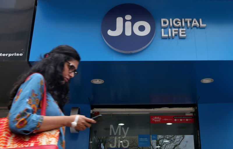 FILE PHOTO: A woman checks her mobile phone as she walks past a mobile store of Reliance Industries' Jio telecoms unit in Mumbai