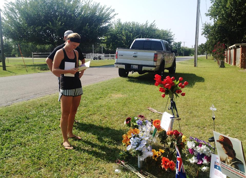 """Sarah Harper,Christopher Lane's girlfriend, stands beside a memorial along the road where police say Lane, an Australian baseball player was shot and killed Friday, Aug. 16, 2013 by three """"bored"""" teenagers who decided to kill someone for fun, in Duncan, Okla. Lane, who was visiting Duncan where Harper and her family lives, had jogged past a home where the boys were staying and that apparently led to him being gunned down at random, said Police Chief Danny Ford. (AP Photo/Kristi Easton)"""