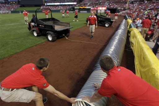 Members of the grounds crew put the tarp on the field before a baseball game between the St. Louis Cardinals and the San Francisco Giants on Friday, May 31, 2013, in St. Louis. (AP Photo/Jeff Roberson)