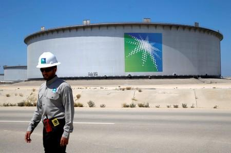 An Aramco employee walks near an oil tank at Saudi Aramco's Ras Tanura oil refinery and oil terminal