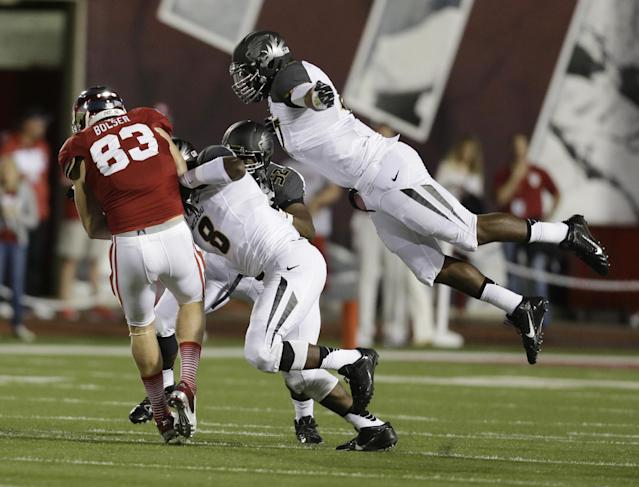 Missouri's Kony Ealy, right, (47) leaps to tackle Indiana's Ted Bolser (83) following a reception during the first half of an NCAA college football game Saturday, Sept. 21, 2013, in Bloomington, Ind. Missouri's Donovan Bonner (8) also was in on the tackle. (AP Photo/Darron Cummings)