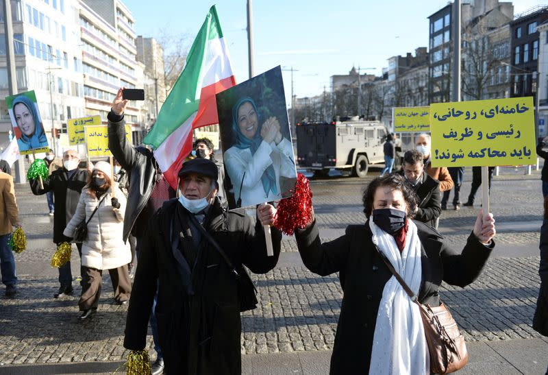 Iranian people hold signs as they protest outside the court building in Antwerp