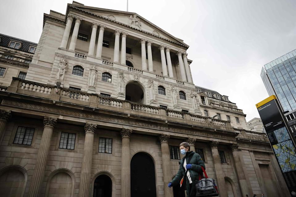 <p>A person walks by the Bank of England wearing a mask as the Chancellor is set to reveal a vaccine funding boost in his Budget</p> (AFP via Getty Images)