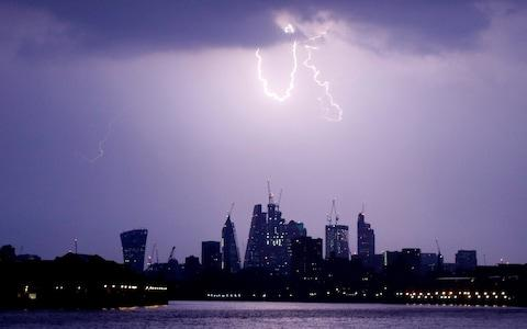 General view as lightning strikes over the City of London - Credit: REUTERS/Tom Jacobs