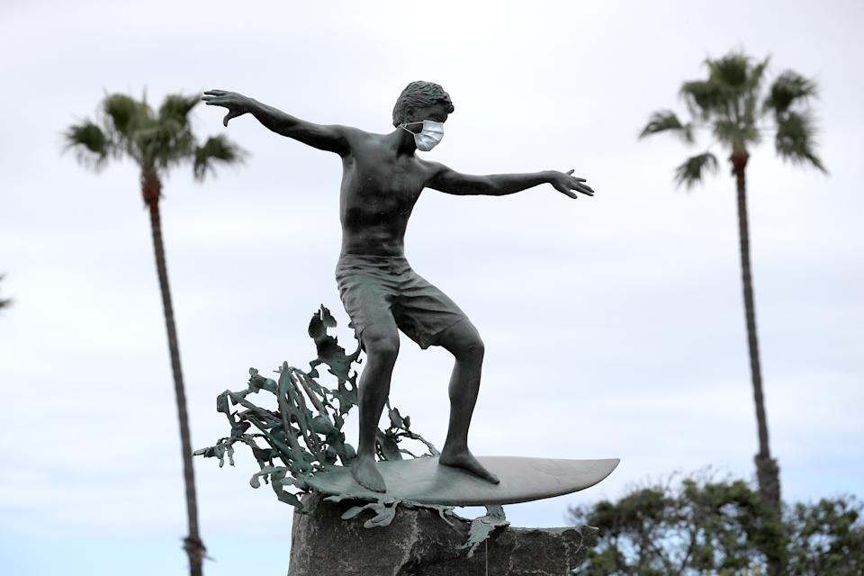 """The """"Magic Carpet Ride"""" statue in Cardiff-by-the-Sea, California wears a face mask to ward off the coronavirus. (Photo: Sean M. Haffey/Getty Images)"""