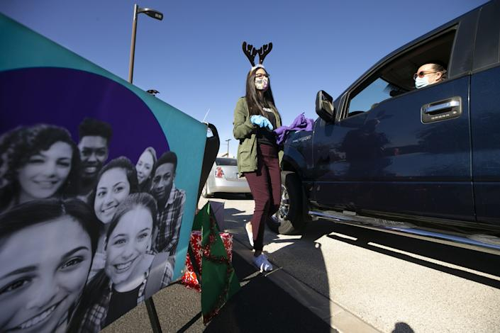Mary Ordonez, an outreach advocate with Bloom365, hands out literature and gifts during a drive-thru holiday open house at the Peoria Community Center in Phoenix. Bloom365 provides outreach for youth impacted by domestic and sexual violence.