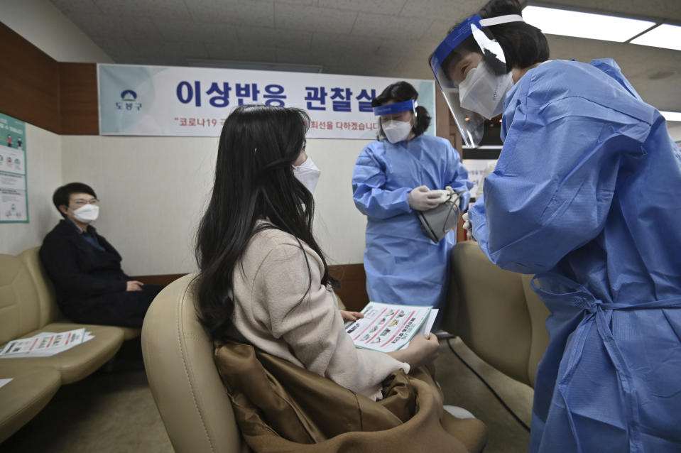 A medical staff, right, checks a nursing home worker after receiving the first dose of the AstraZeneca COVID-19 vaccine at a health care center in Seoul Friday, Feb. 26, 2021. South Korea on Friday administered its first available shots of coronavirus vaccines to people at long-term care facilities, launching a mass immunization campaign that health authorities hope will restore some level of normalcy by the end of the year. (Jung Yeon-je /Pool Photo via AP)
