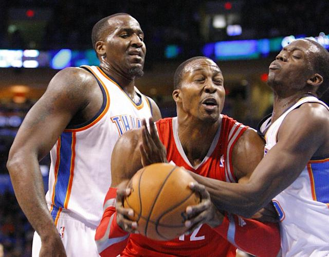 Houston Rockets center Dwight Howard goes to the basket between Oklahoma City Thunder's Kendrick Perkins, left, and Reggie Jackson, right, during the first quarter of an NBA basketball game, Sunday, Dec. 29, 2013, in Oklahoma City. (AP Photo/Alonzo Adams)