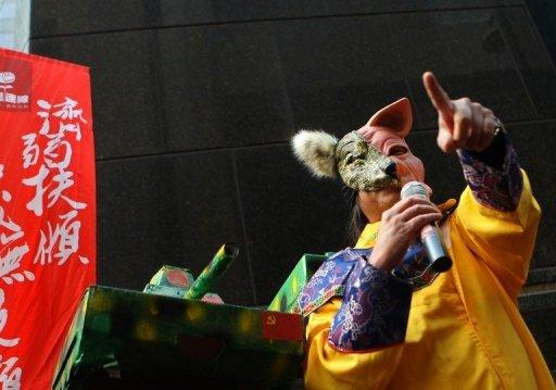 File photo shows Leung Kwok-hung wearing a yellow emperor suit and a pig-wolf mask -- depicting then-Chief Executive candidates Leung Chun-ying as a wolf and Henry Tang as a pig -- next to a papier-mache Chinese tank as he leads a protest denouncing the government's voting system during Hong Kong's Chief Executive Election in March