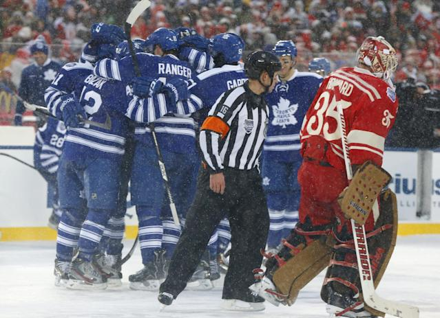 Detroit Red Wings goalie Jimmy Howard (35) skates by as the Toronto Maple Leafs celebrate their 3-2 win in a shootout at the Winter Classic outdoor NHL hockey game at Michigan Stadium in Ann Arbor, Mich., Wednesday, Jan. 1, 2014. (AP Photo/Paul Sancya)