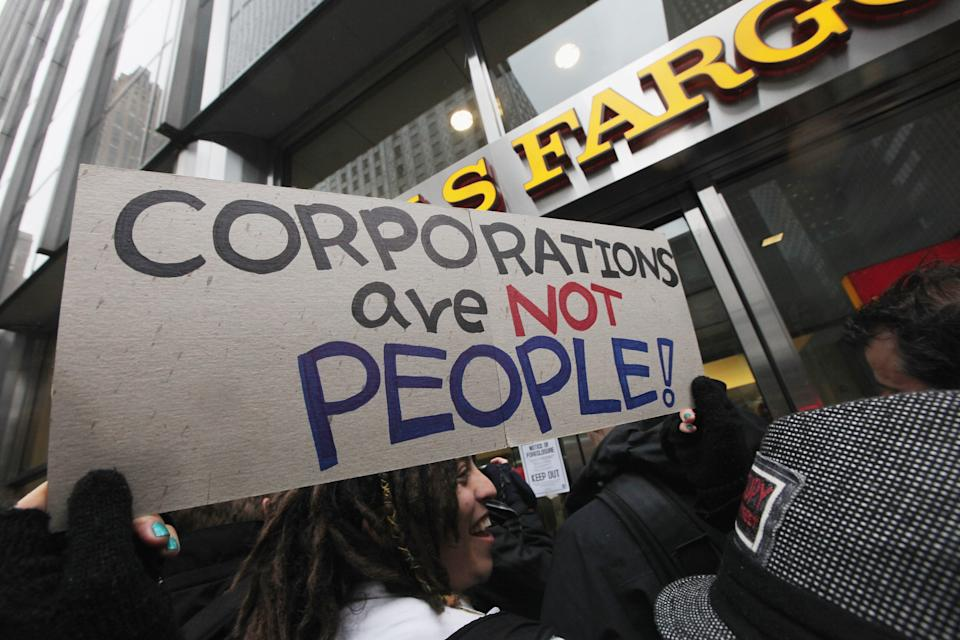 "NEW YORK, NY - FEBRUARY 29: Protesters demonstrate in front of a Wells Fargo bank branch during an Occupy Wall Street ""Shut Down the Corporations"" protest on February 29, 2012 in New York City. Occupy movements across the country are planning protests in dozens of cities against corporate power. (Photo by Mario Tama/Getty Images)"