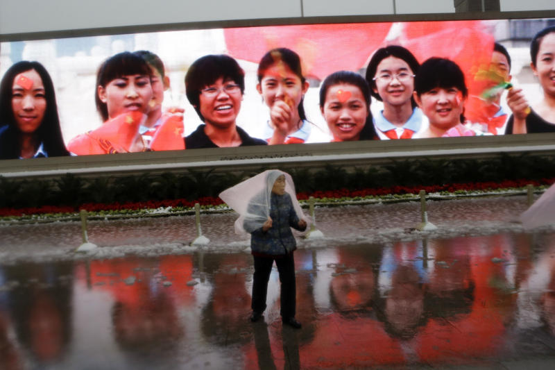 "FILE - In this Sunday, Nov. 4, 2012, file photo, an elderly woman uses a plastic sheet to cover herself from the rain as she walks past a screen showing younger women near the Great Hall of the People in Beijing. A Chinese proverb calls filial piety, or respect for one's parents, ""the first among 100 virtues."" The ancient philosopher Confucius credited it as the bedrock of social harmony, and a popular song urges grown children to visit their parents often. (AP Photo/Ng Han Guan, File)"