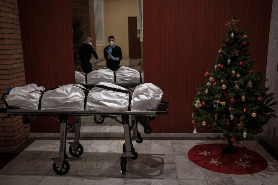 Mortuary workers take off their protective clothing at the entrance of a building decorated with a Christmas tree, after removing the body of person who is suspected of dying from COVID-19 in Barcelona, Spain, Dec. 23, 2020. The image was part of a series by Associated Press photographer Emilio Morenatti that won the 2021 Pulitzer Prize for feature photography. (AP Photo/Emilio Morenatti)