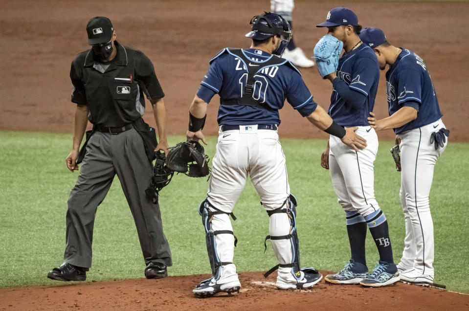 Home plate umpire Gabe Morales, left breaks up a meeting on the mound between Tampa Bay Rays' Mike Zunino (10), Luis Patino and Willy Adames, right, during the third inning of a baseball game against the New York Yankees Tuesday, May 11, 2021, in St. Petersburg, Fla. (AP Photo/Steve Nesius)