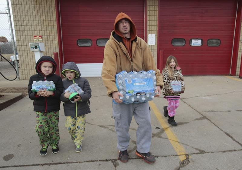 Flint resident Jerry Adkisson and his children carry water bottles from a fire station. (Photo: Rebecca Cook / Reuters)