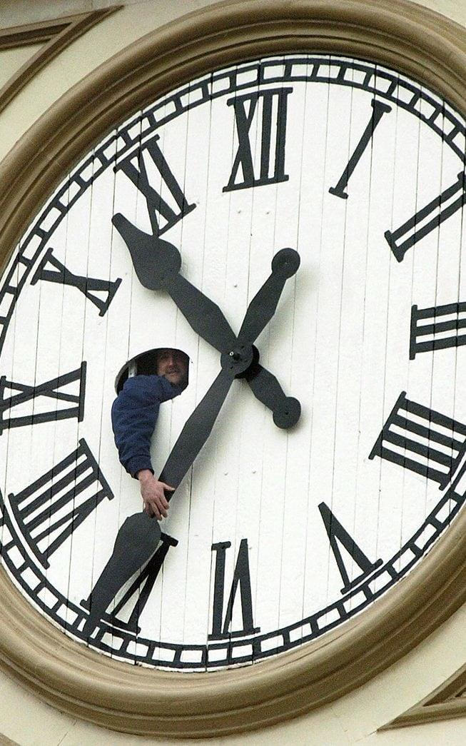 Worker Bill Harper manually moves time ahead on the Market Hall Clock Tower in downtown Peterborough, Ontario back in April, 2004 - Credit: AP