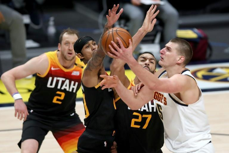 Denver's Nikola Jokic (R) drives to the basket against Utah's Joe Ingles (L), Jordan Clarkson (2L) and Rudy Gobert in the Nuggets' 128-117 NBA victory over the Jazz