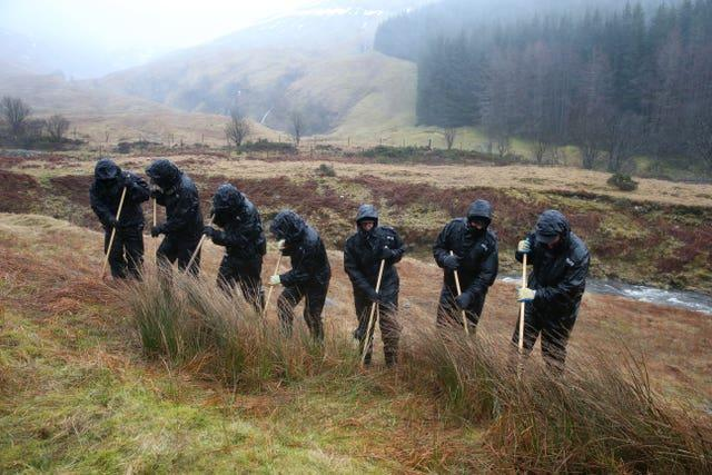 Police officers search undergrowth in a valley on the outskirts of Tyndrum