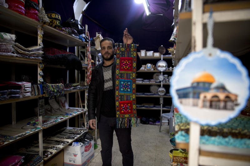 In this Wednesday, Feb. 12, 2020 photo, Palestinian shopkeeper Abdelkarim al-Karaki poses for a photo in his store, which carries souvenirs by artisans engaged in traditional handicrafts, but about half the products in his shop come from China, including refrigerator magnets with pictures of Jerusalem and embroidered wall hangings, in the West Bank city of Hebron. The local market has long been flooded by low-cost Chinese goods. Traders fear that if the outbreak and quarantine efforts continue they will have to switch to more expensive alternatives, passing higher prices onto consumers who may not be able to bear them. (AP Photo/Majdi Mohammed)