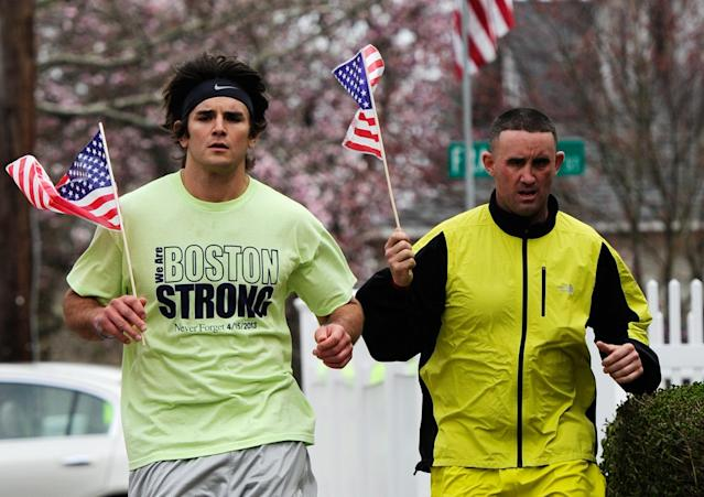 WATERTOWN, MA - APRIL 20: Mike Coppola (L) and Eric Wayne run by Franklin Street with American flags and a 'Boston Strong' t-shirt on April 20, 2013 in Watertown, Massachusetts. A manhunt for Dzhokhar A. Tsarnaev, 19, a suspect in the Boston Marathon bombing ended after he was apprehended on a boat parked on a residential property in Watertown, Massachusetts. His brother Tamerlan Tsarnaev, 26, the other suspect, was shot and killed after a car chase and shootout with police. The bombing, on April 15 at the finish line of the marathon, killed three people and wounded at least 170 (Photo by Kevork Djansezian/Getty Images)