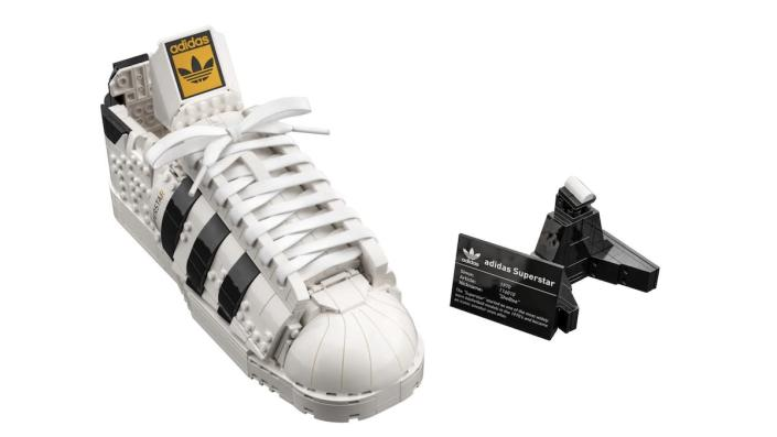 A white and black LEGo replica of an adidas sneaker next to a small plaque and display stand