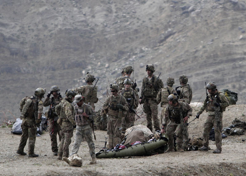 U.S. soldiers evacuate a dead body as they arrive to the scene after a NATO helicopter crashed in a field killing two American service members, near Gerakhel, eastern Afghanistan, Tuesday, April 9, 2013. The U.S.-led International Security Assistance Force said the cause of the crash is under investigation but initial reporting indicates there was no enemy activity in the area at the time. It did not immediately identify the nationalities of those killed. But a senior U.S. official confirmed they were Americans. (AP Photo/Rahmat Gul)