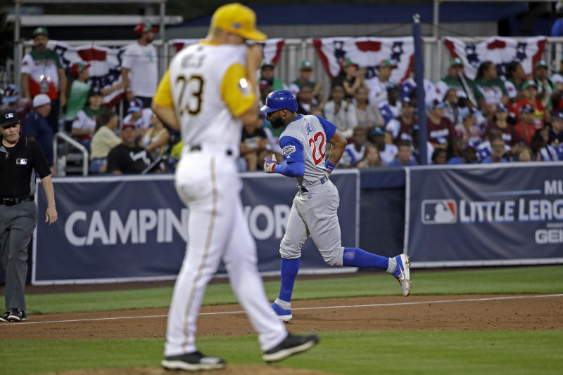 Pittsburgh Pirates starting pitcher Mitch Keller, foreground, collects himself on the mound as Chicago Cubs' Jason Heyward (22) rounds third base after hitting a solo home run during the third inning of the Little League Classic baseball game at Bowman Stadium in Williamsport, Pa., Sunday, Aug. 18, 2019. (AP Photo/Tom E. Puskar)