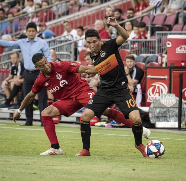 Houston Dynamo midfielder Tomas Martinez (10) maneuvers around Toronto FC defender Justin Morrow (2) during the first half of an MLS soccer game, Saturday, July 20, 2019 in Toronto. (Christopher Katsarov/The Canadian Press via AP)