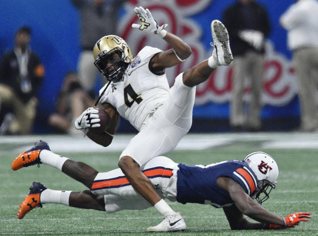"Auburn defensive back Javaris Davis (13) tackles Central Florida wide receiver <a class=""link rapid-noclick-resp"" href=""/ncaaf/players/244577/"" data-ylk=""slk:Tre'Quan Smith"">Tre'Quan Smith</a> (4) during the first half of the Peach Bowl NCAA college football game, Monday, Jan. 1, 2018, in Atlanta. (AP Photo/Mike Stewart)"