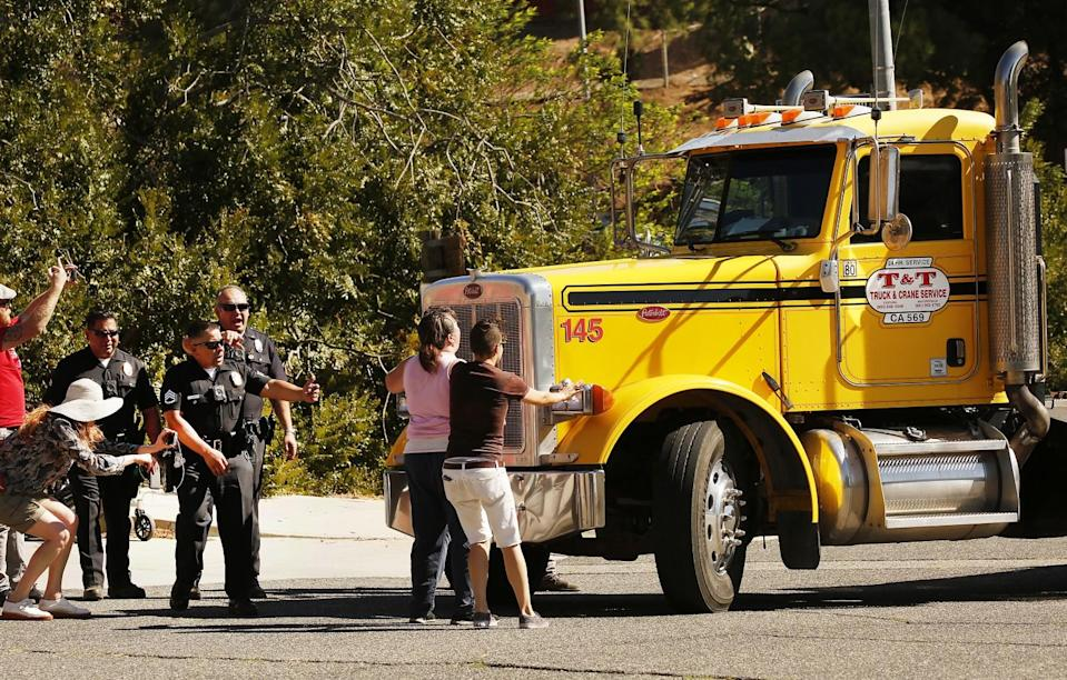 Protesters and LAPD officers confront a semitruck driver that screeched to a halt in front of a protest.