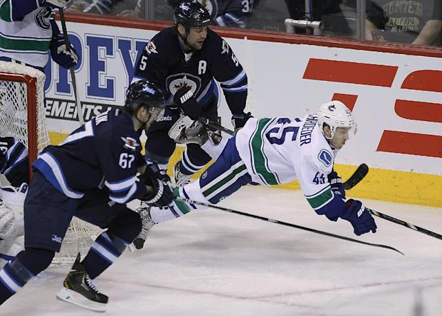 Vancouver Canucks' Jordan Schroeder (45) gets tripped by Winnipeg Jets' Michael Frolik (67) and Mark Stuart (5) during the first period of an NHL hockey game Wednesday, March 12, 2014, in Winnipeg, Manitoba. (AP Photo/The Canadian Press, John Woods)