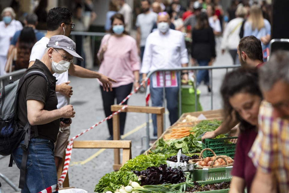 People wearing face masks to protect against coronavirus walk, during the reopening of the Saturday market, in Lausanne, Switzerland, Saturday, May 23, 2020 as lockdown measures due to the coronavirus were eased. (Laurent Gillieron/Keystone via AP)