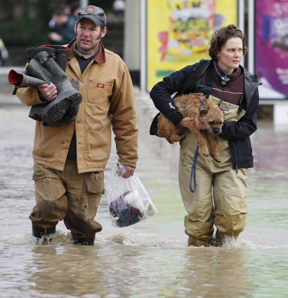 A woman carries her dog as she makes her way through flood waters in St. Asaph, North Wales, Tuesday Nov. 27, 2012, after the town flooded overnight. Thousands of drivers and residents face further chaos today after heavy rain continued to fall across Britain. (AP Photo/PA, Dave Thompson) UNITED KINGDOM OUT NO SALES NO ARCHIVE