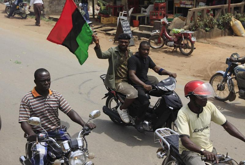 In this photo taken Wednesday, Feb. 29, 2012, Igbo men ride on a motorbike carrying a Biafra flag on a street in Nnewi, Nigeria. Assaults by a radical Islamist sect known as Boko Haram have sent many Igbo people to flee the north even as state officials and others downplay the exodus, likely out of fear of sparking retaliatory violence. (AP Photos/Sunday Alamba)