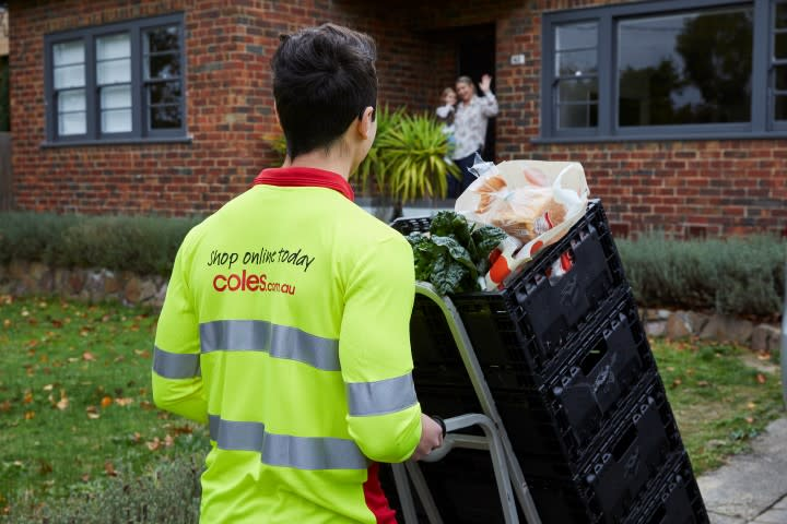 A Coles delivery driver arrives at a woman's home as she waves to him. He's pushing crates.