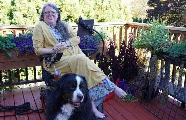 Michelle Hewitt is the co-chair of the organization Disability Without Poverty. The former public school math and music teacher and principal was diagnosed with multiple sclerosis in her early 40s. Her dog's name is Deefer. (Joseph Otoo/CBC News - image credit)