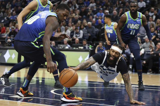 Minnesota Timberwolves' James Johnson, front right, lunges for the ball against Dallas Mavericks' Dorian Finney-Smith, front left, in the first half of an NBA basketball game Sunday, March 1, 2020, in Minneapolis. (AP Photo/Stacy Bengs)