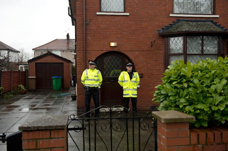 Police officers stand guard outside the family home of one of nine British citizens detained by Turkish authorities for allegedly attempting to illegally enter Syria