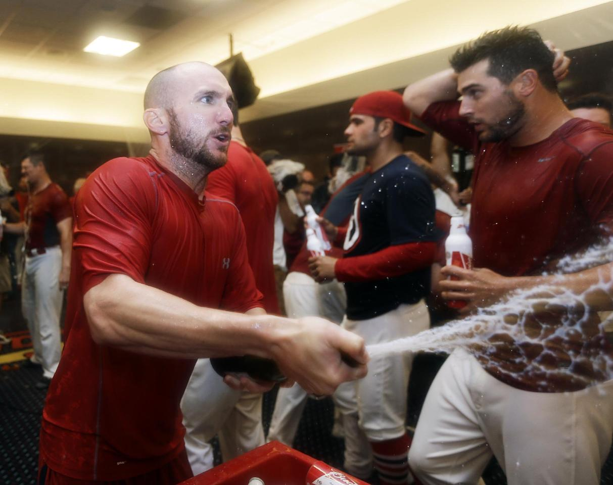 St. Louis Cardinals' Shane Robinson, left, celebrates after the Cardinals beat the Pittsburgh Pirates 6-1 in Game 5 in a National League baseball division series, Wednesday, Oct. 9, 2013, in St. Louis. The Cardinals advanced to the NL championship series against the Los Angeles Dodgers. (AP Photo/Jeff Roberson)