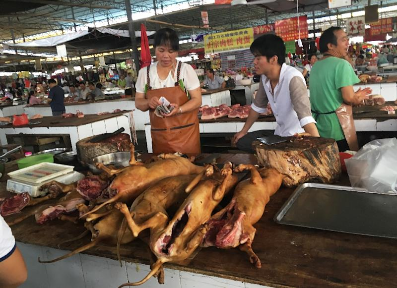 Vendors stand behind a pile of dog meat at the Nanqiao market in Yulin (AFP Photo/BECKY DAVIS)