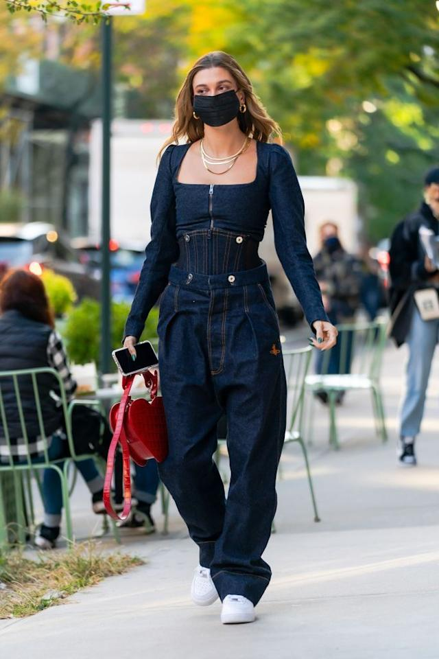 """<p>Hailey Bieber stepped out in a denim <a href=""""https://www.net-a-porter.com/en-gb/shop/designer/vivienne-westwood"""" target=""""_blank"""">Vivienne Westwood</a> two piece, pairing the structured corset to with baggy boyfriend jeans. The model added her signature gold jewellery with a red Westwood bag and some <a href=""""https://www.asos.com/nike/nike-air-force-1-07-lv8-2fa20-trainers-in-triple-white/prd/20622813"""" target=""""_blank"""">Nike Air Force 1</a>s. </p><p>The 23-year-old wore <a href=""""https://www.elle.com/uk/fashion/celebrity-style/a30377203/hailey-bieber-wedding-dress-fittings-photos/"""" target=""""_blank"""">Westwood to her wedding rehearsal in summer of last year</a>, proving the designer is a favourite of the former dancer.</p>"""