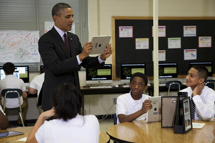 President Barack Obama records students on a classroom iPad while visiting a seventh grade classroom before speaking about goals of connecting students to next generation broadband and wireless technology within five years, Tuesday, Feb. 4, 2014, at Buck Lodge Middle School in Adelphi, Md. (AP Photo/Jacquelyn Martin)