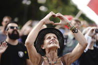 A participant forms a heart with her hands during a demonstration against the corona measures of the German Government in Berlin, Germany, Saturday, Aug. 29, 2020. (Kay Nietfeld/dpa via AP)