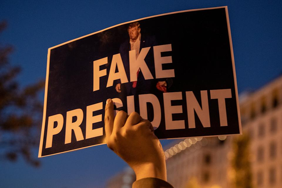 "Un hombre sujeta un letrero en Washington en el que se lee sobre una foto de Trump: ""Fake President"" (""Presidente Falso""). (Foto: Chris McGrath / Getty Images)."