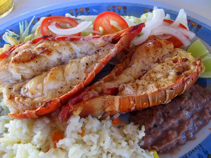 This November 2012 photo shows fresh grilled lobster at a popular lunch spot known as Velasquez Restaurant after just being caught in the sea off Isla Mujeres, Mexico. Isla Mujeres, or Island of Women, is a tiny 5-mile-long, half-mile wide island just a half-hour's ferry ride across from Cancun, with far fewer visitors and a much calmer, romantic atmosphere. (AP Photo/Amanda Lee Myers)