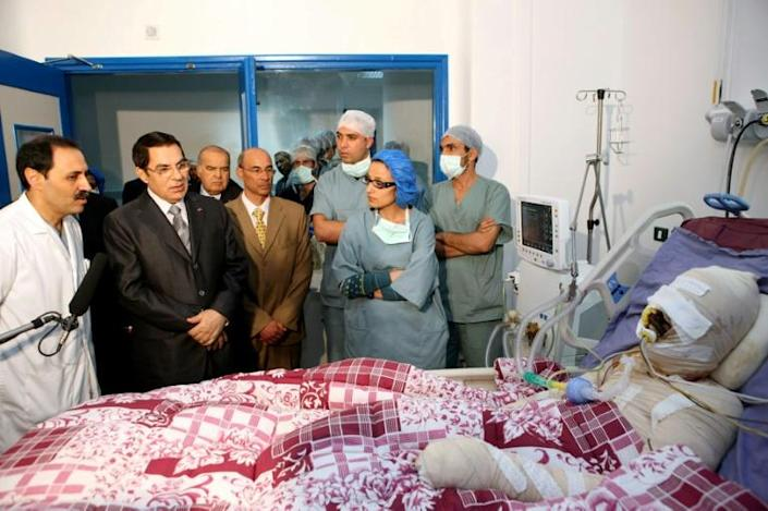 A handout picture from the Tunisian Presidency shows Ben Ali visiting Mohamed Bouazizi at a Tunis hospital in December 2010. Bouazizi died a month after self-immolating in protest at unemployment and police harassment, triggering a nation-wide revolt (AFP Photo/TUNISIA PRESIDENCY)