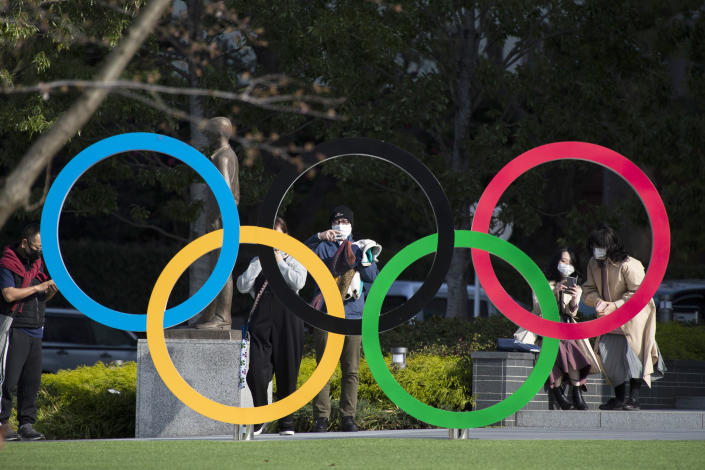 FILE - In this March 19, 2021, file photo, people take pictures of the Olympic rings installed by the Japan Olympic Museum in Tokyo. The vaccine rollout in Japan has been very slow with less than 1% vaccinated. This of course is spilling over to concerns about the postponed Tokyo Olympics that open in just over three months.(AP Photo/Hiro Komae, File)